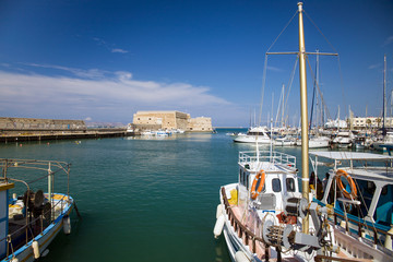 Boats and motorboats under the walls of Koules Fortress in Heraklion.Fortress on the sea, tourist attraction of the city of Heraklion. Historic building in Crete, Greece.