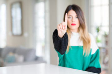 Young beautiful woman wearing winter sweater at home Pointing with finger up and angry expression