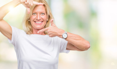 Middle age blonde woman over isolated background smiling making frame with hands and fingers with happy face. Creativity and photography concept.