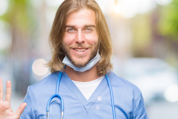 Young handsome doctor man with long hair over isolated background showing and pointing up with fingers number five while smiling confident and happy.