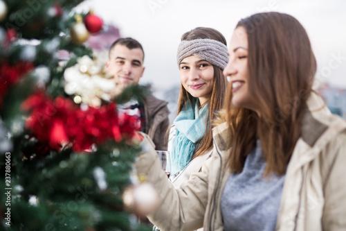 Fotos Cena Navidad Frinsa.Young Friends Decorating Christmas Tree On Balcony Stock
