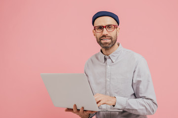 Photo of guy internet user browses website on laptop computer, connected to wireless internet, holds electronic gadget, wears spectacles, formal shirt, isolated over pink background with free space