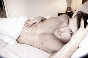 Handsome naked man with six pack abs and blue eyes lying in hotel room bed
