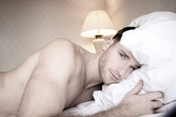 Handsome muscular naked men with blue eyes lying on hotel bed sheets looking at camera
