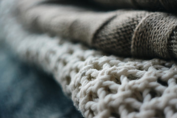 three sweaters of different colors and type of weaving are in a pile with a blurred background