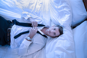 Handsome exhausted business man lying on hotel room bed looking up as he unties his tie