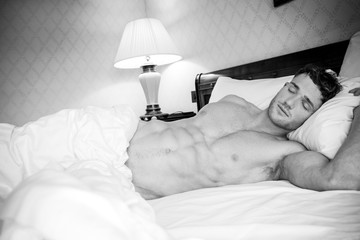 Handsome hunky muscular man with six pack abs sleeping in between white sheets in hotel bed