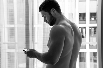 Handsome hunky shirtless man using mobile phone next to balcony with city view