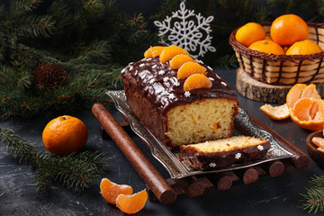 Cupcake with tangerines, covered with chocolate glaze is located on the New Year's or Christmas background