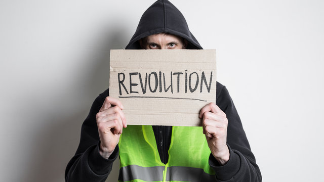 A man in a yellow vest holds a cardboard with the inscription revolution