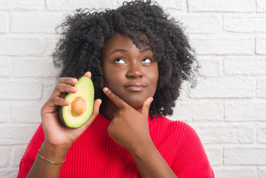 Young african american woman over white brick wall eating avocado serious face thinking about question, very confused idea