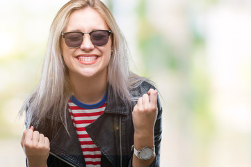Young blonde woman wearing fashion jacket and sunglasses over isolated background very happy and excited doing winner gesture with arms raised, smiling and screaming for success. Celebration concept.