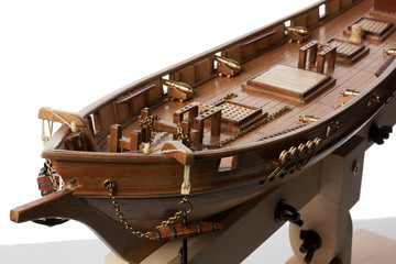 Assembling a model of a sailing ship made of wood on a white background.