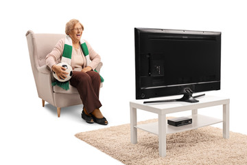 Happy senior woman sitting in an armchair with soccer ball and watching a game on TV