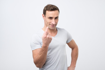 Handsome young man showing come here gesture with index finger and smiling over gray background.