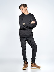 Teenage boy dressed in black trendy clothes posing at studio.