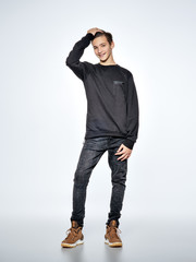 Cheerful teenage boy dressed in black trendy clothes posing at studio.