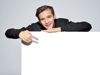 Teen boy is pointing by finger to empty white banner