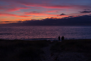Silhouette of three people at beach sunset in Normandy, France