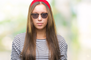 Young beautiful caucasian woman wearing sunglasses over isolated background with serious expression on face. Simple and natural looking at the camera.