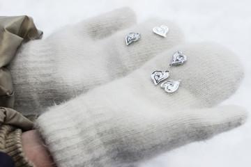 Children's hands in winter gloves hold hearts