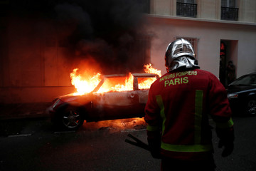 """A fireman stands next to a burning car during clashes at a demonstration by the """"yellow vests"""" movement in Paris"""