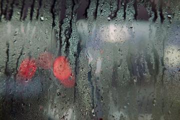 red lights seen through wet windshield during rainfall Wall mural