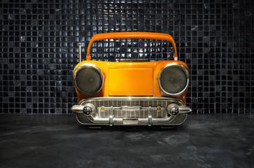 Old antique car shape AM FM stereo cassette player on mosaic tiles background