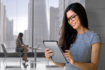 Business woman with smart pad tablet at office space with skyline in background
