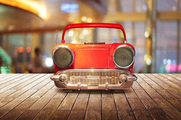 Old antique car shape AM FM stereo cassette player on wood table top with blur background
