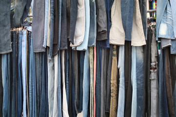 Many jeans hanging on a clothesline.