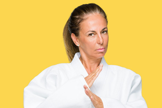 Middle age adult woman wearing karate kimono uniform over isolated background with serious expression on face. Simple and natural looking at the camera.