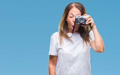 Middle age hispanic woman taking pictures using vintage photo camera over isolated background scared in shock with a surprise face, afraid and excited with fear expression