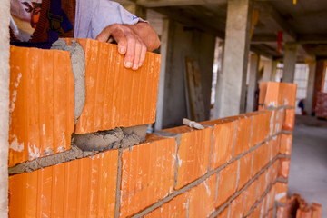 Worker is building wall with red blocks and mortar