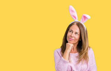 Middle age brunette woman wearing easter rabbit ears over isolated background with hand on chin thinking about question, pensive expression. Smiling with thoughtful face. Doubt concept.