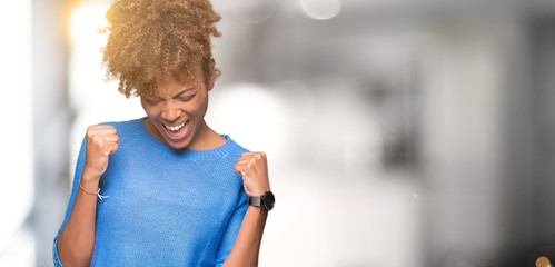 Beautiful young african american woman over isolated background very happy and excited doing winner gesture with arms raised, smiling and screaming for success. Celebration concept.