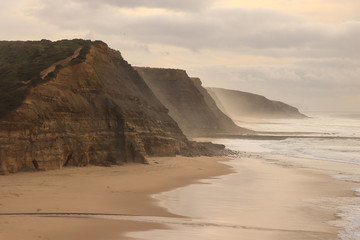 Aerial view from a sandy beach at the sunset with an amazing cliff. Portugal