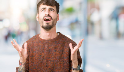 Young handsome man wearing winter sweater over isolated background crazy and mad shouting and yelling with aggressive expression and arms raised. Frustration concept.