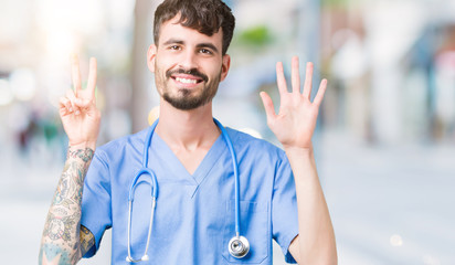 Young handsome nurse man wearing surgeon uniform over isolated background showing and pointing up with fingers number seven while smiling confident and happy.