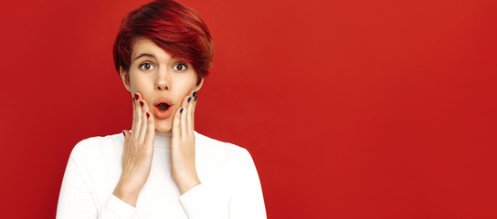Woman portrait. Emotions. Shocked. Girl with short red hair is touching her cheeks and looking at camera with an open mouth, on a red background