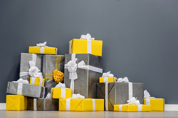 A pile of yellow and grey Christmas gifts with ribbons against the wall on a beautiful hardwood floor with copyspace Wall mural