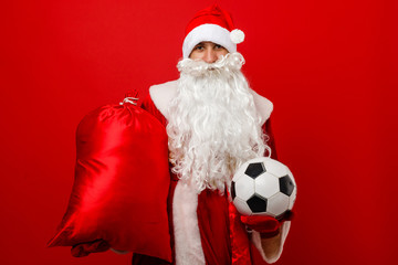 Santa holds a classic football against red background