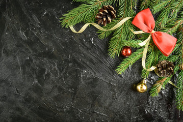 Christmas decoration. Fir-tree branch with balls, pine cone and bows on a black background