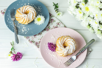 Delicious cakes with coconut chips on pink and gray plate on white table