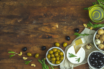 Cheese camembert, black and green olives, quail eggs on plates, olive oil and rosemary, cashew nuts