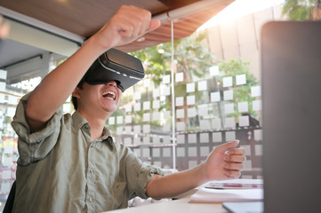 Man wearing virtual reality goggles in modern office excited technology concept.