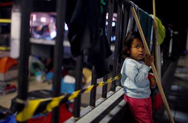 A migrant, part of a caravan of thousands from Central America trying to reach the United States, stands in a temporary shelter in Tijuana