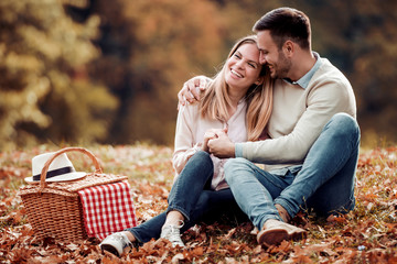 Couple in love sitting in autumn park