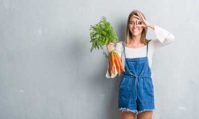 Fototapeta Beautiful young woman over grunge grey wall holding fresh carrots with happy face smiling doing ok sign with hand on eye looking through fingers obraz