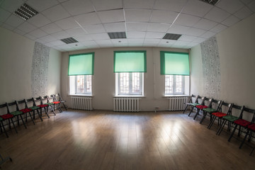 Empty dark room with three windows on wall, chairs standing on the sides and wooden hardfloor, nobody